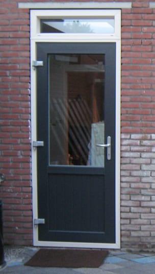 Kunststof achterdeur met borstwering uitgevoerd in antraciet grijs met houtnerfstructuur, aluminiumkleurige deurklinken en in 3 richtingen verstelbare scharnieren